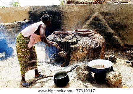 A Woman Lights Firewood