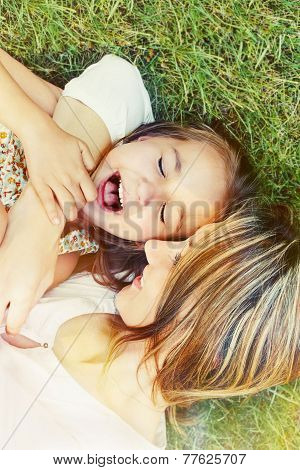 Happy Little Girl And Her Mother Having Fun Outdoors On The Grass In Sunny Day