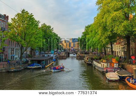 Amsterdam Canal With The Boat Rowers In The Evening Light, Holland, Netherlands.
