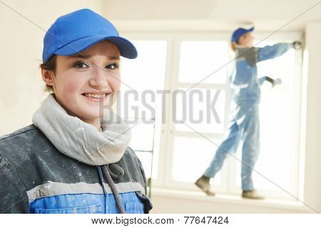 female plasterer painter portrait at indoor wall renovation decoration stopping with spatula and plaster poster