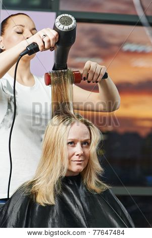 hairdresser drying hair with blow dryer of woman client at beauty parlour after highlighting poster
