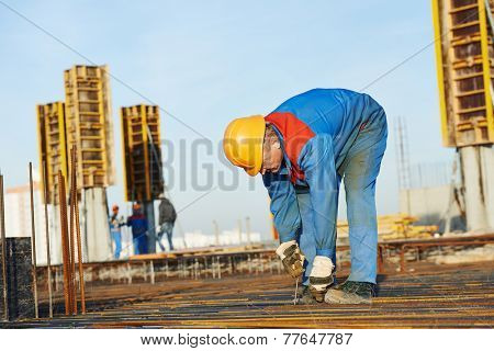 builder worker knitting metal rebars into framework reinforcement for concrete pouring at construction site