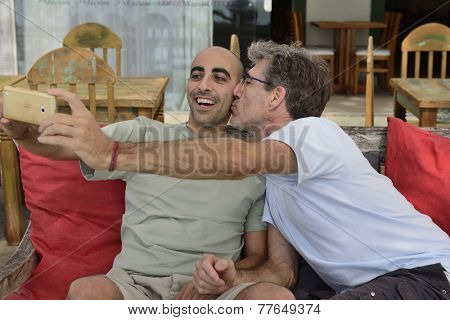 Gay couple taking a selfie with mobile phone in a cafe