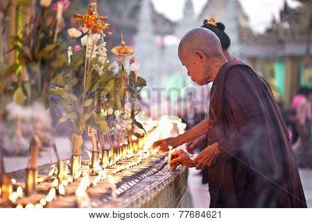 YANGON, MYANMAR - JANUARY 29 :A buddhist nun pours oil in for oil lamp at Shwedagon temple Jan 29, 2010, Myanmar to celebrate the full moon festival.