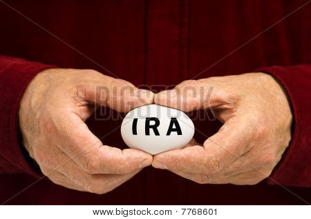 Man Holds White Nest Egg With IRA On It