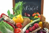Colorful mix of many different fresh vegetables in a basket with a board poster