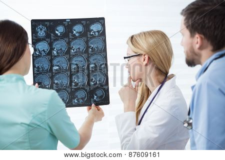 Three experienced physicians checking head magnetic resonance image poster