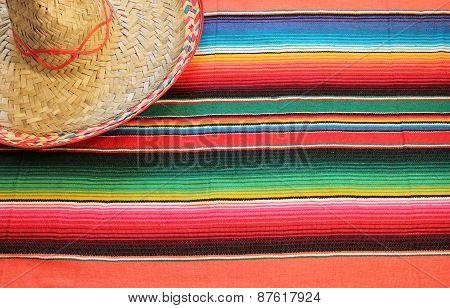 fiesta mexican poncho rug in bright colors with sombrero background with copy space cinco de mayo, dias de los muertos, day of the dead,