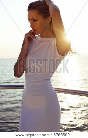 Sensual Woman With Blond Hair In Elegant White Dress Posing On Yacht