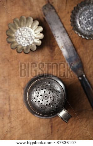 Vintage  Baking utensils - sifter, spatula, tins and moulds on wooden board