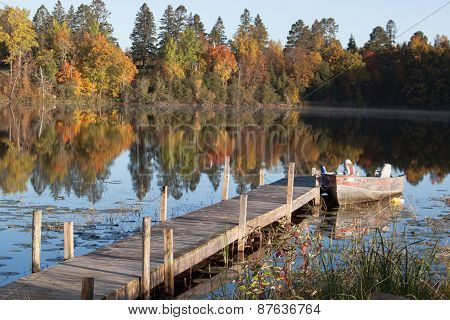 boat and dock on lake in the fall