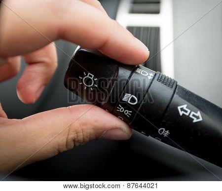 Closeup Of Man Adjusting Light Control Toggle In Car