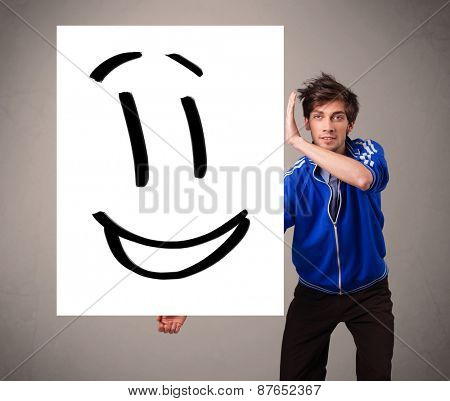 Handsome young boy holding smiley face drawing