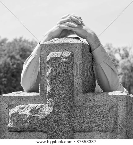 Black and white lone figure of person's hands grieving at cemetery poster