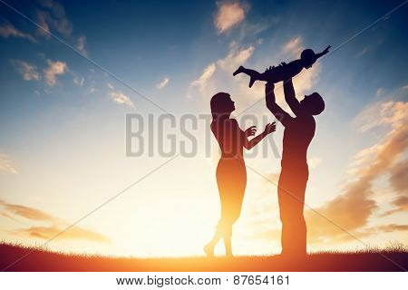 Happy family together, parents with their little child at sunset. Father raising baby up in the air.