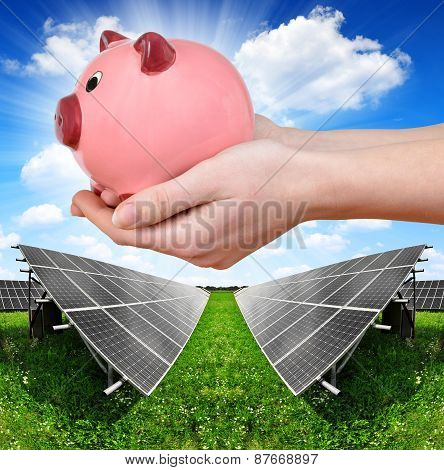 Solar panels and hand holding a pink piggy bank