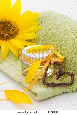 little glass jar of beauty treatment on green towel poster