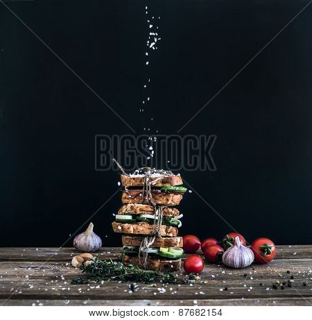 Sandwiches With Smoked Meat, Tomato, Garlic, Cucumber And Herbs Tied By Rope, Placed One Over Anothe