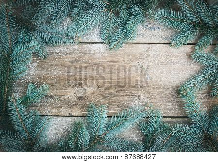 Christmas (new Year) Theme Background: A Frame Of Fur-tree Branches Over A Rough Wooden Desk