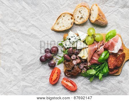 Meat And Cheese Plate On Rustic Wood Board Over A White Paper Background
