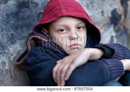 homeless young boy leaned against the wall poster