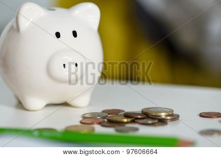 Pile Of Different Coins Near White Piggybank On Table