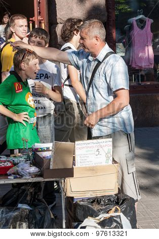 Kiev, Ukraine - May 25, 2013: Street Vendor Trifle Chinese Production Demonstrates Their Goods On Th