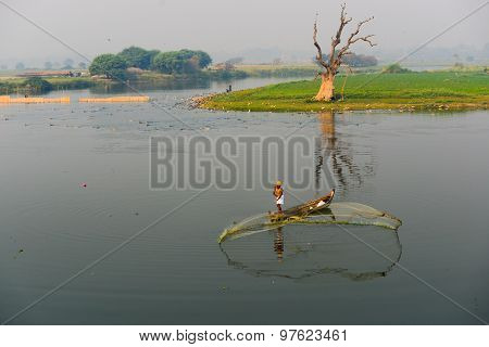 MANDALAY - FEB 28, 2015 : A man throw net for catching fish near U-Bein bridge in Mandalay, Myanmar. The U-Bein bridge is the longest teak bridge in the world