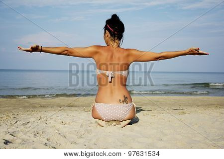Woman On Beach Sitting And Spreading Her Arms