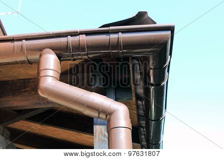 brown rain gutter on a home against blue sky