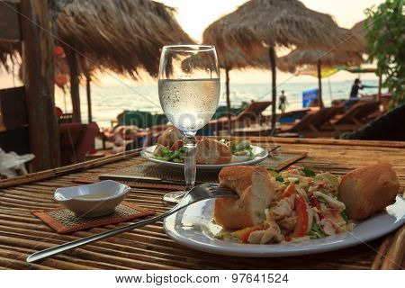 Beach Evening On The Sunset With Glass Of Water And Dinner