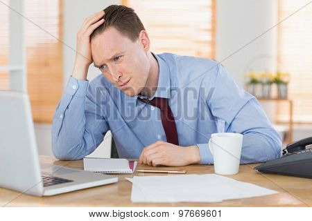Stressed businessman working at his desk in his office