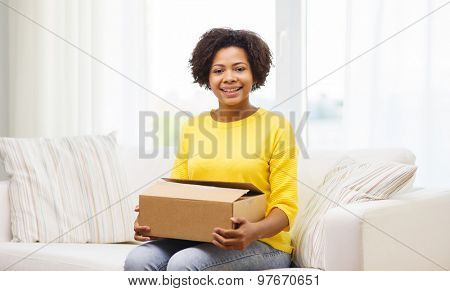 people, delivery, shipping and postal service concept - happy african american young woman holding open cardboard box or parcel at home