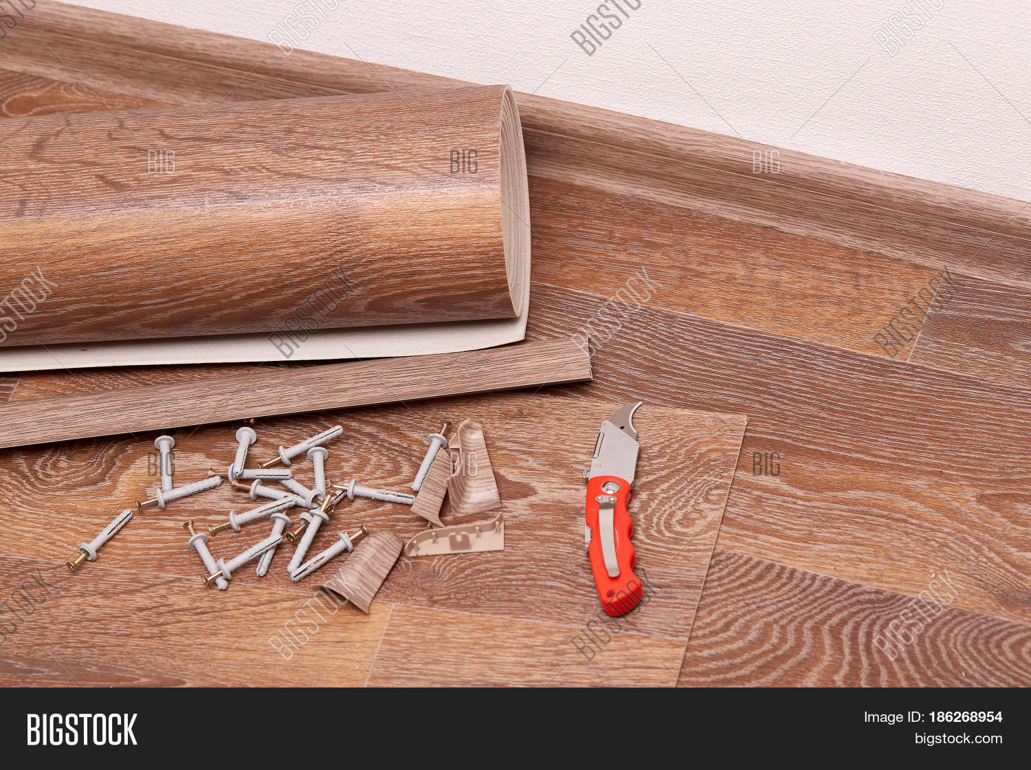 A Roll Of Linoleum Baseboards Fasteners Are Laying On The New Floor Covering