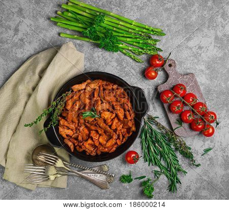 Meat cut into strips. Pan with meat goulash stroganoff meal. Ingredients for goulash stroganoff rosemary thyme parsley asparagus cherry tomatoes. Dark black shabby background. Top view