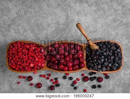 Various frozen berries Red currants blueberries cherries. On gray stone background berries are red blue. A measuring spoon for frozen berries. Top view empty copy space.