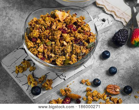 Healthy breakfast vitamin snack Granola - rolled oats and diet concept. Ingredients for the granola are pecans blueberries red berries walnuts. Milk for the granola. Gray stone background.
