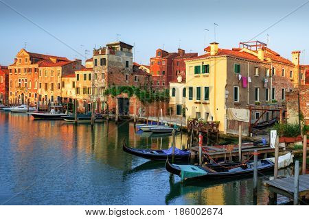 Amazing view on morning Venice. Row of boats and glowing colourful houses. Italy, Europe