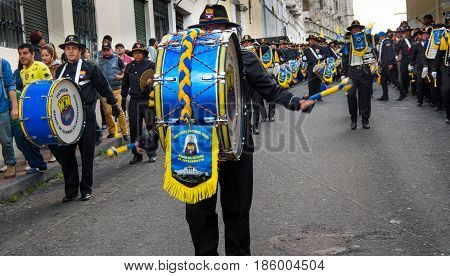 Quito, Ecuador - December 09, 2016: An unidentified man playing a drum while unidentified people is watching the parade in Quito, Ecuador.