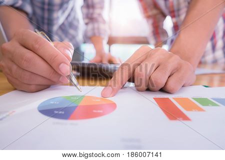 Business team pointing the turnover graph chart while discussion in office.