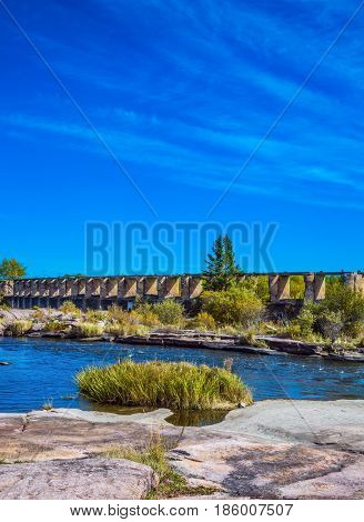 The ruins of old dam in Old Pinawa Dam Park. Indian summer in Manitoba, Canada. The concept of ecological and recreational tourism