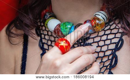 Close up of caucasian woman's hand with red ring showing colorful necklaces on a neck