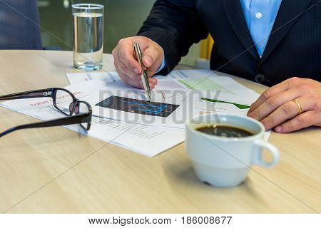 Businessman Working On Charts On A Wood Table, Pointing An Expensive Silver Pen, With Glasses, Coffe