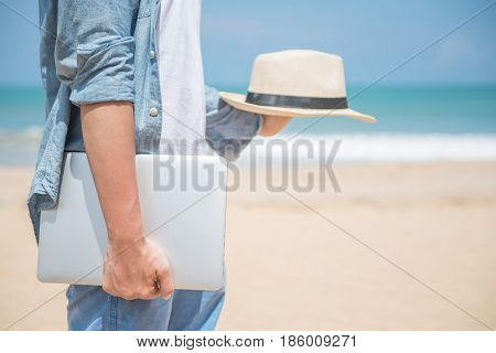 Man hand holding laptop and hat on tropical beach working outdoor in summer season digital nomad lifestyle concepts