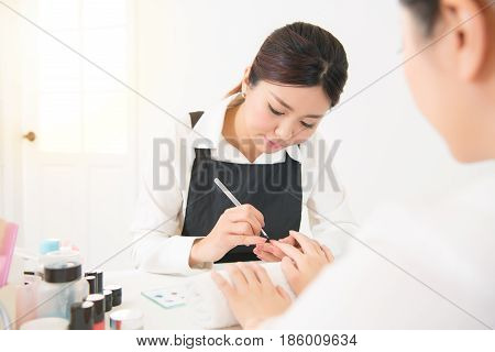 Beautician Hand Painting Nails Of Woman