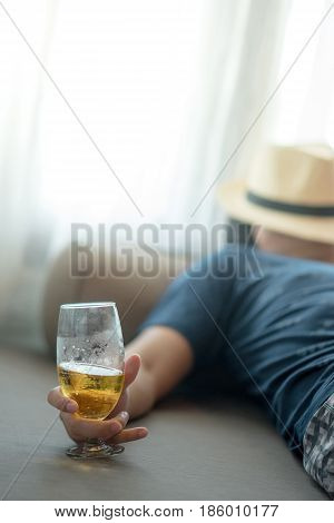 drunken man sleeping while holding a glass of beer in bedroom hangover after holiday party alcoholism or alcohol addiction concepts