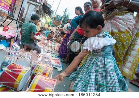KOLKATA WEST BENGAL INDIA - 12TH AUGUST 2012 : Indian girl child choosing musical products from out door local market place. India is boomimg with middle class consumers in society.