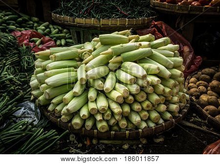 Baby corn stacked on top of bamboo webbing in the middle various kind of vegetables photo taken in Bogor traditional market java