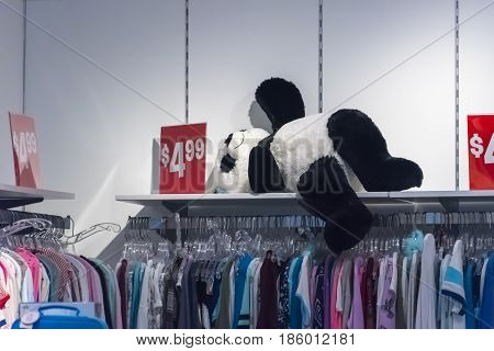 Black and white tossed on an upper shelve appears to be sleeping in a department store for children