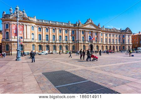 TOULOUSE FRANCE - MARCH 26 2017 : Tourists walking in the Capitole de Toulouse Facade of the Capitol the City Hall of Toulouse France
